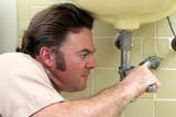 plumber tightening pipe poster
