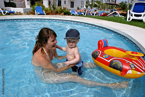 young mother playing in children's swimming pool with toddler so