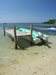 boat by pier at low tide at coast of roatan