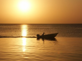sunset with man in boat on roatan island
