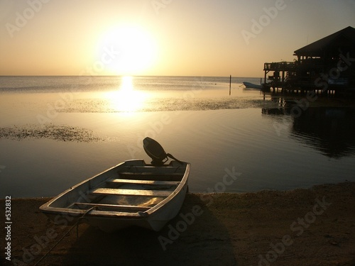 sunset with boat on roatan island