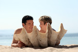 romantic couple on the beach behind the seashell poster