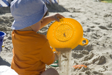 toddler with toys on sand