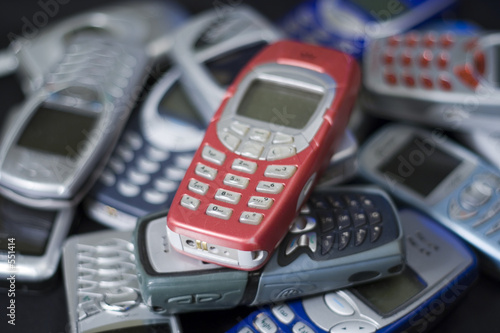 red cellular phone on heap of others. - 551414