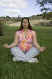 pregnant woman meditating on grass