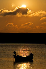 fishing boat moored at sea during sunset