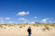 young mother and son walking along sunny sandy beach in spain
