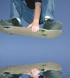youth jumping over water on skateboard deck poster