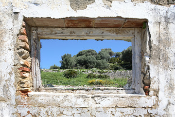 spanish countryside seen through hole in wall of ruins