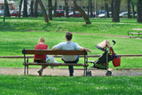 couple with a baby carriage resting in the park poster