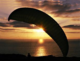 hang glider against sunset