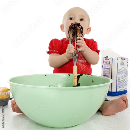 baby licking cake mixer