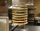 pizzas in rack  (focus on pizzas) poster