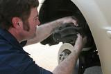 mechanic inserting brake pad poster