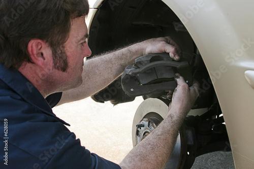 poster of mechanic inserting brake pad