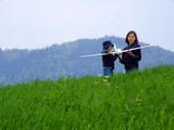 two girls on the green hill with airplane poster