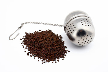 tea and stainless steel tea ball on white backgrou