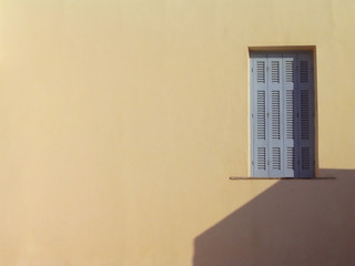 window on beige wall.  santorini, greece