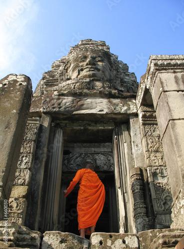 a monk enters bayon temple at angkor thom, cambodi