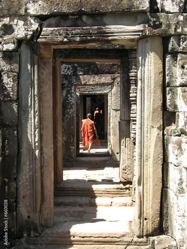 monks walk through passageways at bantaey kdei, an