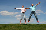 couple jumping against blue sky poster