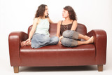 young women sitting on sofa and chating poster