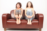 two young women sitting on sofa and watching tv poster