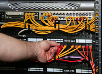 technician plugs a network cable into a patch pane