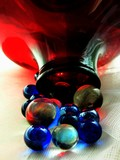 deep-red glass pot and glass blue balls poster