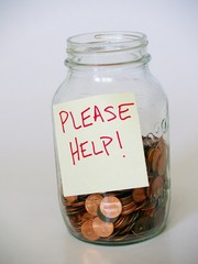 "jar full of pennies with ""please help"" sign"