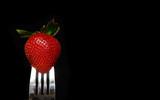 strawberry on fork on black poster