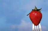strawberry on fork against blue sky poster