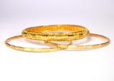 three gold bangles / gold bracelets poster