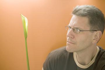 man contemplates calla lily
