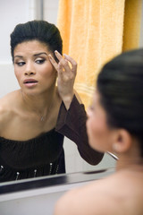 attractive young ethnic girl applying make up