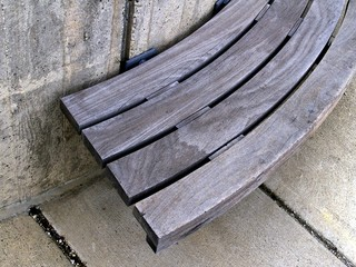 an urban plaza bench of wood and concrete