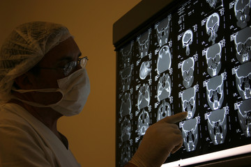 doctor in surgical scrubs looking x-ray