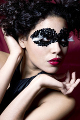 attractive young woman wearing a black gem mask