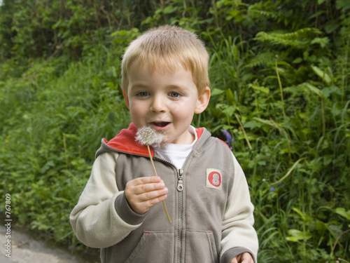 young boy blowing dandelion seeds.