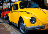a vintage red and yellow  volkswagen beetle parked poster