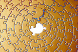 abstract of a golden jigsaw with the missing piece laying above poster