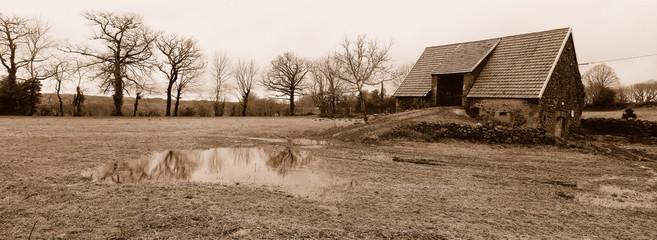 grange ancienne et mare de pluie en auvergne