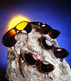 four sunglasses over a nice stone poster