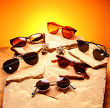 six sunglasses over sand and stones poster