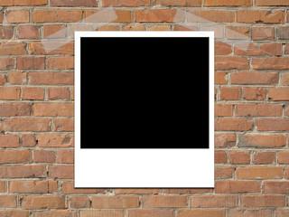 polaroid on brick wall
