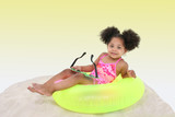 beautiful young girl laying in the sand on floaty poster
