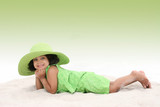 beautiful young girl laying in the sand wearing big green hat poster