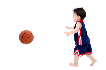 adorable toddler boy playing basketball barefoot over white