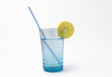 glass of mineral water with lemon and straw on whi