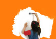 little girl painting an orange wall